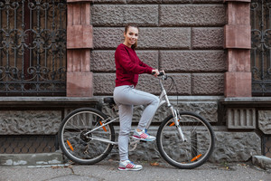 Picture of cheerful woman dressed in sweater walking with her bicycle in the city while standing near wall and smiling. Look at camera.