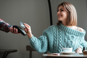 Picture of cheerful young lady dressed in sweater sitting in cafe at cold winter day and pays for her order with debit card. Look aside.