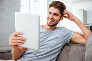 Picture of cheerful young man in grey t-shirt sitting on sofa at home while looking on tablet.