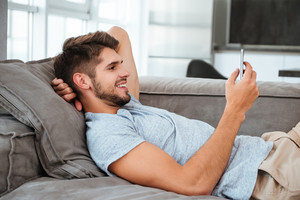 Picture of cheerful young man lies on sofa and looking on phone.