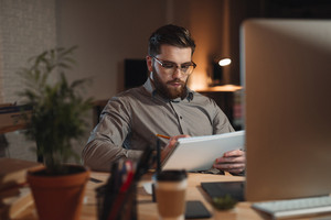 Picture of concentrated bearded designer dressed in shirt working late at night with computer and drawing sketches in album.