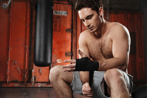 Picture of concentrated man sitting in a gym. Looking at hands.