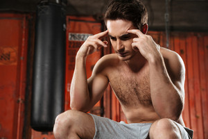 Picture of concentrated man with headache sitting in a gym. Looking aside.