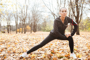 Picture of concentrated runner in warm clothes and headphones looking aside in autumn park while make sport exercise