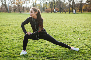 Picture of concentrated sport woman in warm clothes and headphones looking aside in autumn park while make sport exercise
