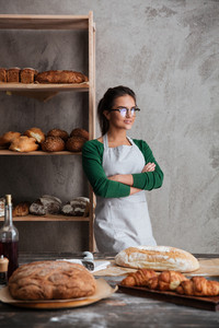 Picture of concentrated young lady baker standing with arms crossed at bakery near bread. Looking aside.