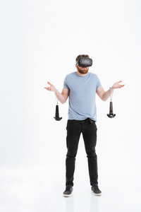 Picture of confused young man wearing virtual reality device standing over white background