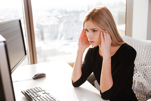 Picture of confused young woman worker sitting in office near computer. Looking at computer.
