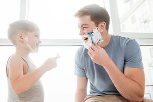 Picture of cute father and son are applying shaving foam on their faces and smiling while shaving in bathroom