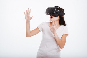 Picture of emotional lady wearing virtual reality device over white background.