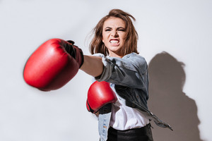 Picture of emotional woman boxer dressed in jeans jacket and gloves make boxing exercise isolated over white background