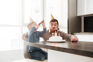 Picture of funny bearded young father sitting near birtday cake with his little son.