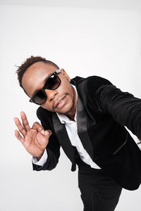 Picture of handsome african businessman wearing glasses make okay gesture. Isolated over white background.