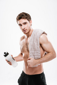 Picture of handsome athlete standing with towel holding bottle of water over white background.