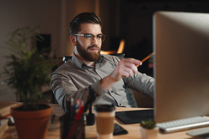 Picture of handsome bearded web designer dressed in shirt working late at night and looking at computer while touching computer display with pencil