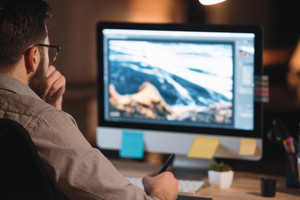 Picture of handsome bearded web designer dressed in shirt working late at night and looking at computer.