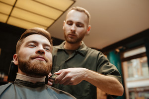 Picture of handsome man getting beard haircut by hairdresser while sitting in chair at barbershop.