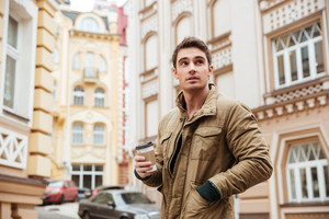 Picture of handsome man walking on the street and looking aside while holding cup of coffee.