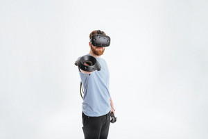 Picture of handsome young bearded man wearing virtual reality device standing over white background while holding joysticks in hands and showing it to camera.