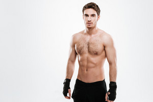Picture of handsome young man boxer standing over white background. Look at camera.