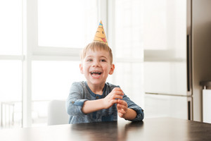 Picture of happy birthday boy sitting in kitchen while smiling. Look aside.