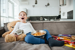 Picture of happy boy on sofa with teddy bear at home playing games by console while eating chips. Holding joystick.
