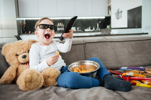 Picture of happy boy on sofa with teddy bear at home watching TV with 3d glasses while eating chips. Holding remote control.