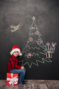 Picture of happy child wearing hat sitting on big gift near Christmas tree drawing on blackboard. Looking at camera.