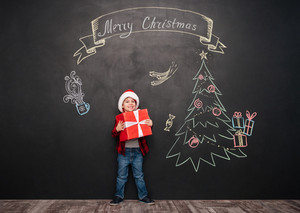 Picture of happy child wearing hat standing near Christmas drawing on blackboard and holding a gift in hands. Looking at camera.