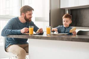 Picture of happy father dressed in blue sweater eating at kitchen with his little son