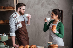 Picture of happy loving couple bakers standing near bread and croissants drinking coffee. Looking aside.