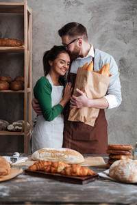 Picture of happy loving couple bakers standing near bread and hugging. Looking aside.