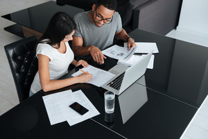 Picture of happy loving young couple using laptop and analyzing their finances with documents. Look at papers.