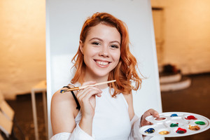 Picture of happy redhead young woman painter standing over blank canvas in artist workshop. Look at camera while holding palette and paintbrush.