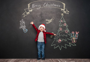 Picture of happy screaming child wearing hat standing near Christmas drawing on blackboard. Looking at camera.