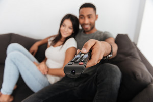 Picture of happy young couple hugging and watching TV on sofa at home. Focus on hand with remote control.