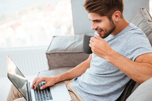 Picture of happy young man in grey t-shirt sitting on sofa at home. Working on laptop computer and smiling while drinking a coffee.