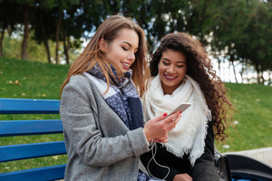 Picture of incredible young ladies sitting on a bench and listening music together on earphones outdoors. Horizontal shot. Looking at phone. With grass on background.