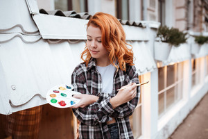 Picture of incredible young lady painter with red hair walking on the street. Look at palette while holding paintbrush outdoors.