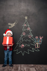 Picture of joyful screaming child wearing hat holding a big gift near Christmas tree drawing on blackboard. Looking at camera.