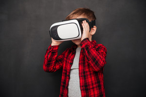 Picture of little child wearing virtual reality device over blackboard while holding the device