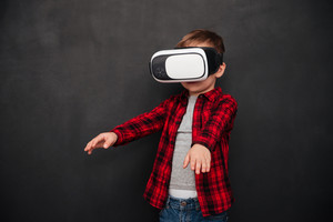 Picture of little child wearing virtual reality device over blackboard