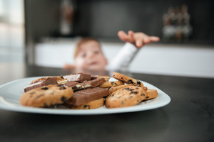 Picture of little cute boy standing in kitchen while tries to eating cookies and chocolate. Focus on cookies.