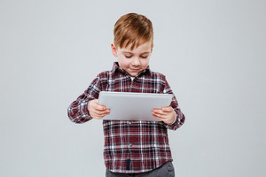 Picture of little happy child standing over grey background holding tablet computer. Look at tablet.