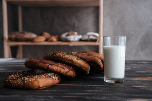 Picture of pastries and glass of milk on dark wooden table