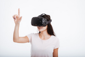 Picture of pretty lady wearing virtual reality device and pointing with finger over white background.