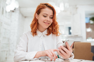 Picture of pretty redhead young woman dressed in white shirt chatting by her phone while sitting in cafe