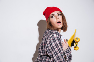 Picture of pretty woman dressed in shirt in a cage print wearing hat standing isolated over white background and holding skateboard
