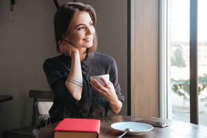 Picture of pretty young lady sitting at the table in cafe near book and drinking coffee. Look aside.