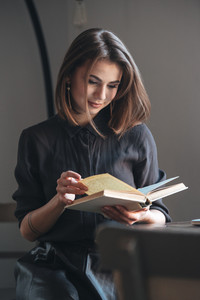 Picture of pretty young woman sitting at the table in cafe and reading book.
